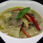 28 Sliced Beef in green curry with coconut milk peas & Thai herbs.